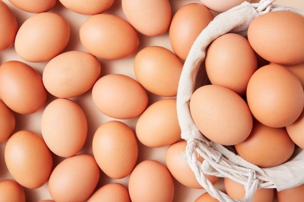 Корзина с домашними яйцами по центру картинки с большим количеством яиц на заднем плане.