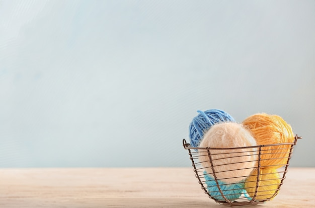 Basket with knitting yarn on table with copy space