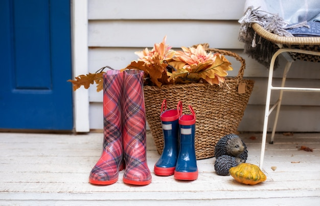 Basket with leaves, pumpkin and rubber boot in yard. checkered and blue rain boots of house on porch