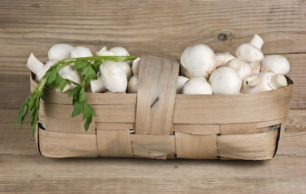 Корзина с грибами на деревянном фоне