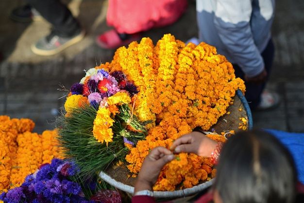 네팔의 광장 시장에서 오렌지 금송화 꽃의 목걸이와 바구니 선택적 초점