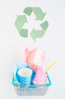 Basket with paper trash and recycle logo