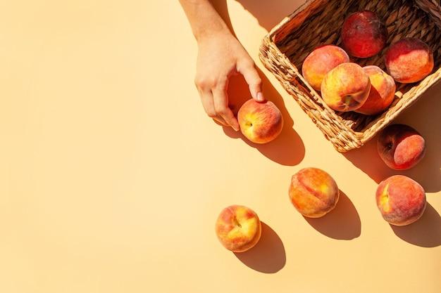 Корзина с персиками на персиковом фоне. трендовые контрастные тени