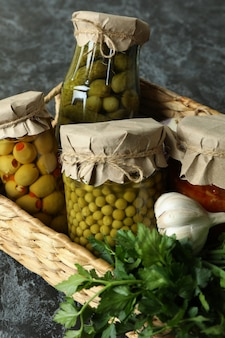 Basket with pickled food and ingredients on black smokey wall