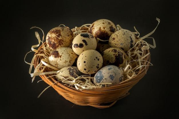 Корзина с перепелиными яйцами, изолированные на черной поверхности