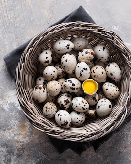 Basket with quail eggs and one cracked