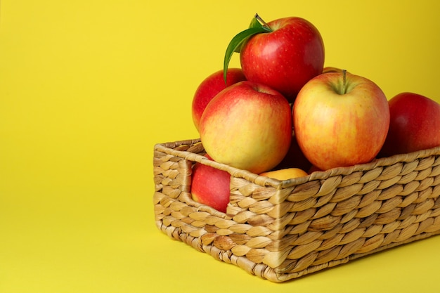 黄色の背景に赤いリンゴのバスケット
