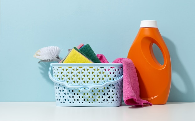Basket with spoges and a brush, next to a plastic orange bottle with liquid detergent on a white table