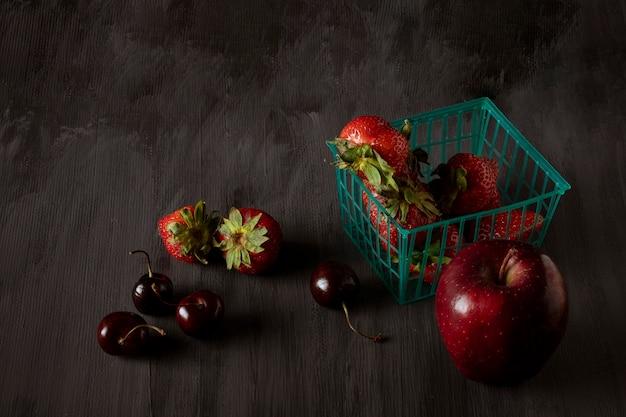 ヴィンテージの木製テーブルブラックの側面にイチゴとリンゴのバスケット
