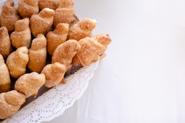 Basket with tasty croissants on white table