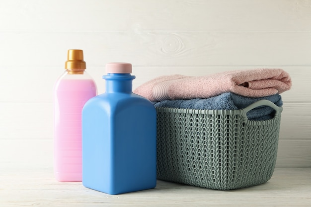 Basket with towels and bottles with laundry liquid on white wooden table