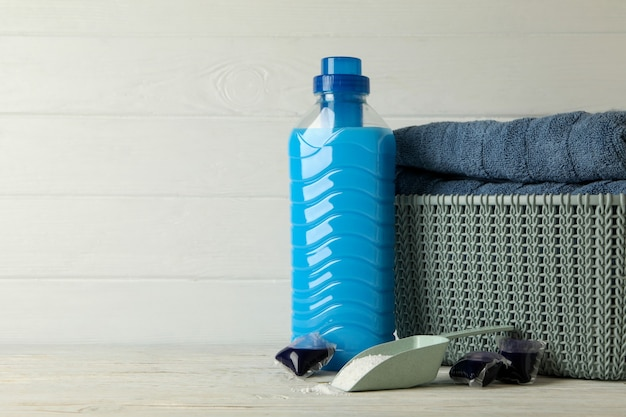 Basket with towels, laundry capsules, scoop with powder and detergent on wooden background