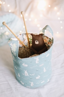 Basket with toys yarn needles knitted clothes against bokeh lights surface in a cozy nursery