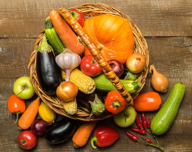Basket with various vegetables over rustic wooden background.