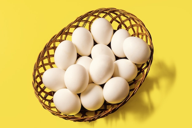 A basket with white eggs on yellow illuminating color