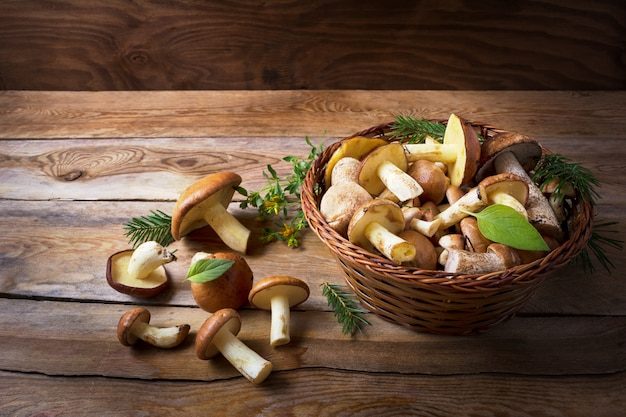 Basket with wild forest mushrooms on the rustic wooden background