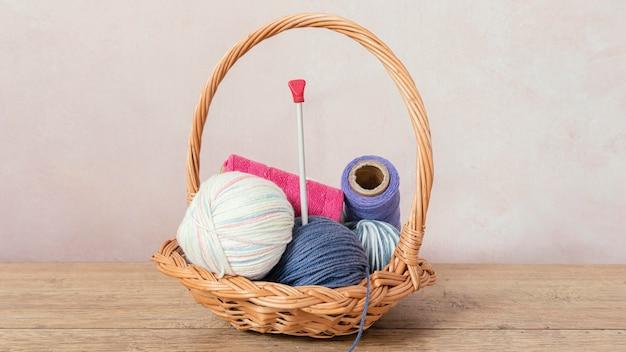 Cesto con lana e ferri da maglia