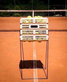 빨간색 테니스 코트에 노란색 테니스 공 바구니.