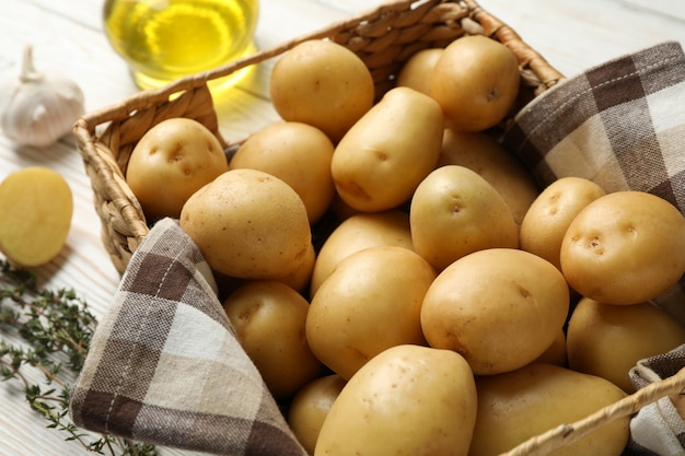 Basket with young potatoes on wooden surface