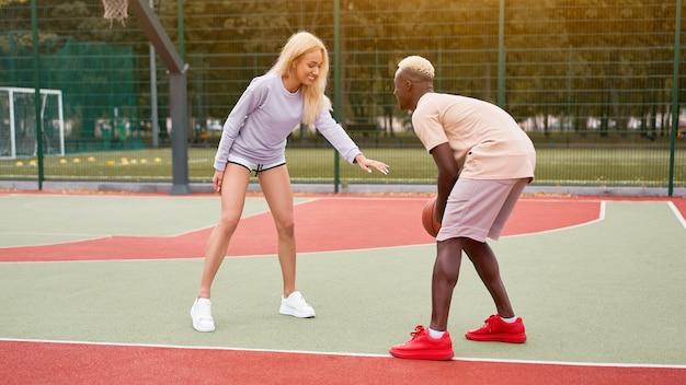 バスケットボールのアフロアメリカ人男性の友人が白人女性を訓練する多民族の友情アフロ男性インストラクターが女性を教える