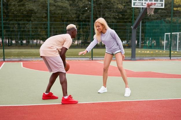 白人女性を訓練するバスケットボールアフロアメリカ人男性の友人