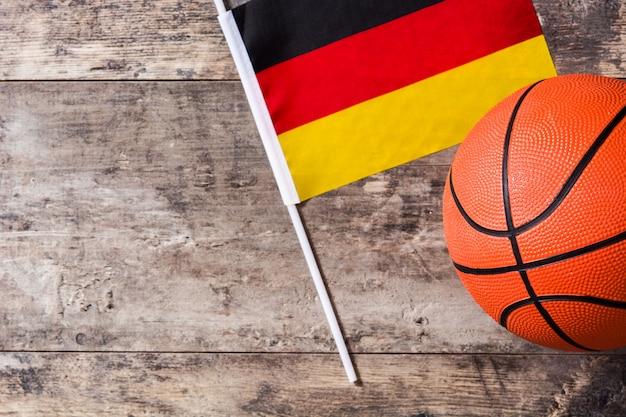 コピースペースを持つ木製のテーブルの上のバスケットボールとドイツの旗
