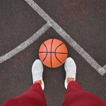 Баскетбол у ног женщины на поле