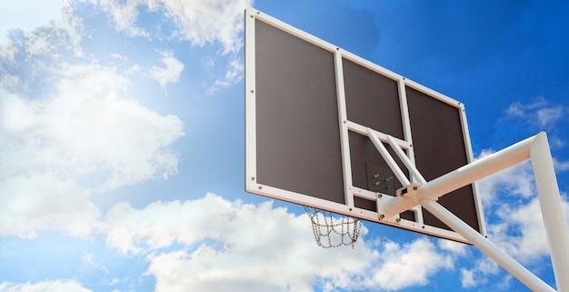 쇠 사슬로 만든 바구니가 있는 농구 백보드, 푸른 하늘을 배경으로 클로즈업. 공간을 복사합니다. 낮은 각도 보기