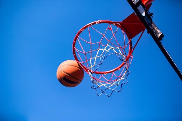 Баскетбольный мяч и обруч, изолированные на голубое небо.