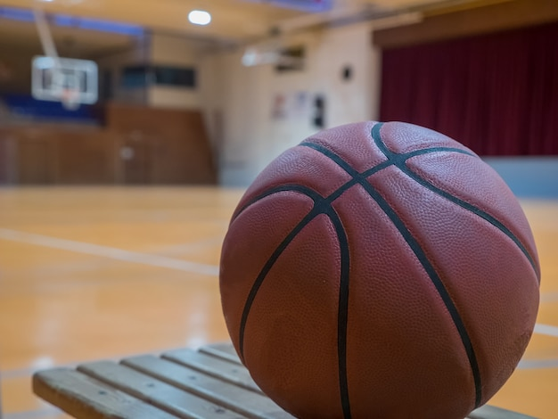 Basketball ball on the court with free throw line ball on the bench for players