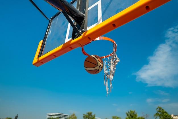 배경에 오래 된 그물 푸른 하늘을 통해 떨어지는 농구 공