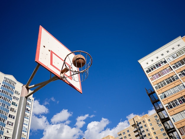 Basketball ball flies into the basket against the background of blue sky and high-rise buildings