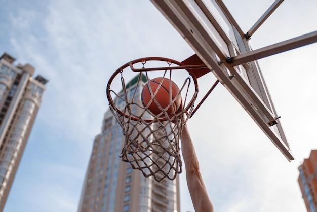 Баскетбольный мяч попадает в корзину на открытом воздухе.
