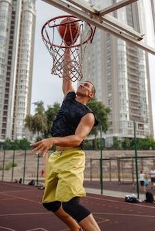 バスケットボールのボールが屋外のバスケットに当たる