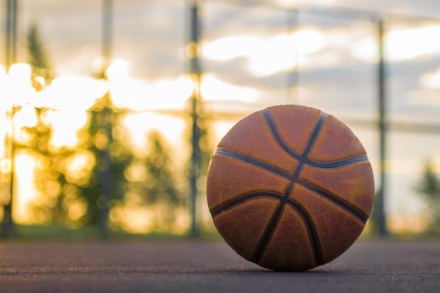 Баскетбольный мяч лежит на земле на фоне вечернего неба. спортивный фон