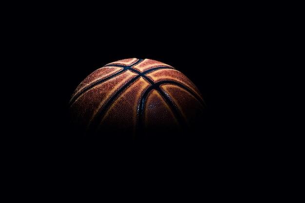 Баскетбольный мяч на черном пространстве.