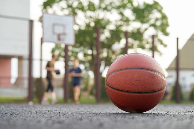 Баскетбольный мяч на улице уличной площадки игроки играют в игру на заднем плане