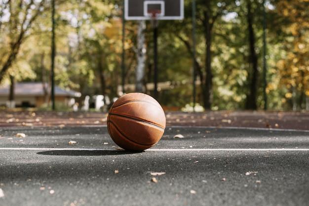 スポーツフィールドのバスケットボールボール。健康的なライフスタイルとスポーツの概念。背景にフープのあるコート。スポーツ用品。