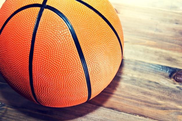 Basketball ball on wooden hardwood floor.