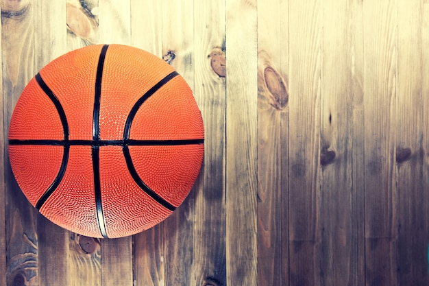 Basketball ball on wooden hardwood floor.