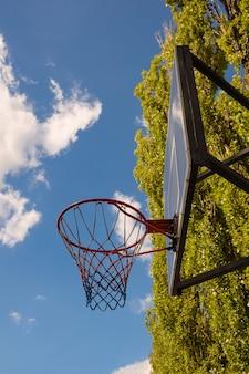 雲と木々と青い空を背景にバスケットボールのバスケットとバックボード。盾の下から、下から撮影