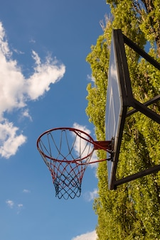 Basketball basket and backboard against the blue sky with clouds and trees. photographed from under the shield, from below