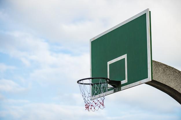 Basketball board with hoop net on blue sky white cloud.