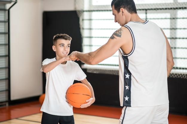 농구. 흰색 운동복 코치와 체육관에서 공을 가진 소년