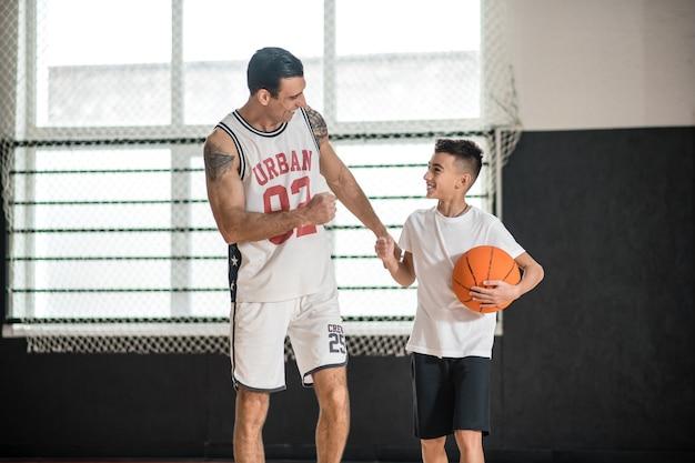 농구. 농구 소년을 가르치는 흰색 운동복 코치