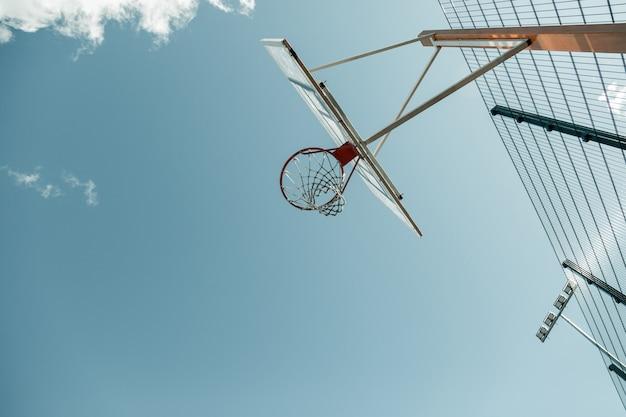 バスケットボールのコート。バスケットボールコートの空のバスケットボールバスケットのローアングル