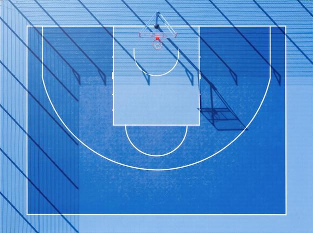 Вид сверху баскетбольной площадки. минималистичный синий корт с длинными тенями при дневном свете с высоты птичьего полета.