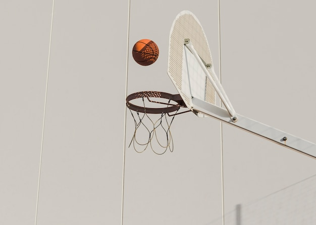 Basketball falling in hoop against wall