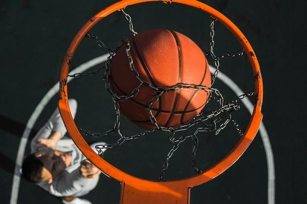Баскетбол падает через кольцо крупным планом
