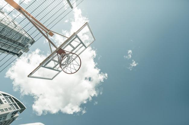 バスケットボールの試合。青い空を背景にバスケットボールのバスケットのローアングル